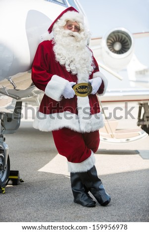 Full length portrait of Santa leaning on private jet at airport terminal - stock photo