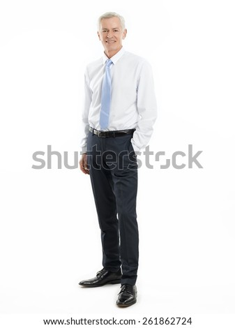 Full length portrait of senior businessman standing against white background while puts his hand in pocket.  - stock photo
