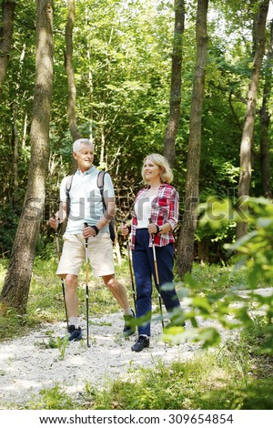Full length portrait of senior couple enjoying a nordic walk. Active elderly woman and man walking on the forest and smiling.