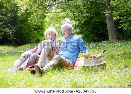Full length portrait of senior couple relaxing outdoor and using digital tablet. - stock photo