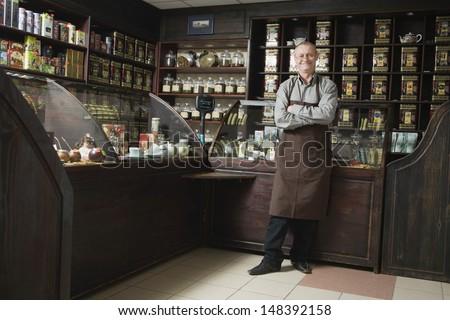 Full length portrait of senior male owner standing in shop - stock photo