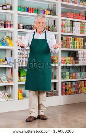 Full length portrait of senior male store owner welcoming in supermarket