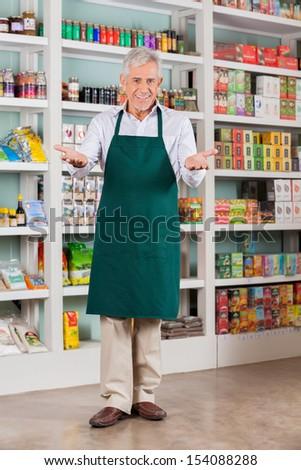 Full length portrait of senior male store owner welcoming in supermarket - stock photo