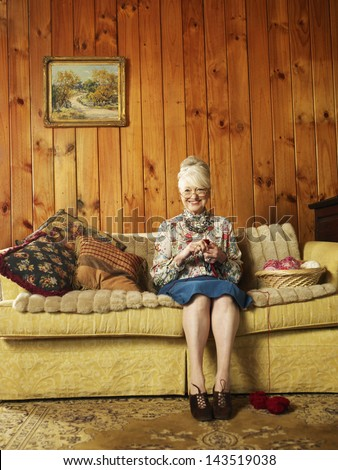 Full length portrait of senior woman sitting on sofa knitting at home - stock photo