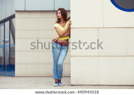 Full length portrait of serious hipster girl wearing trendy  blue jeans, yellow knitted top near beige wall of modern building in summer city. Copy-space. Outdoor shot