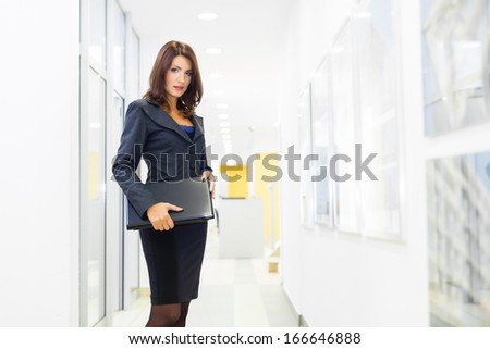Full length portrait of serious young female professional standing with a folder in office lobby - stock photo