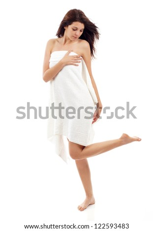Full length portrait of sexy beautiful young woman wrapped in towel with long healthy hair isolated over white background.  Concept of natural beauty care skin, legs, spa bath