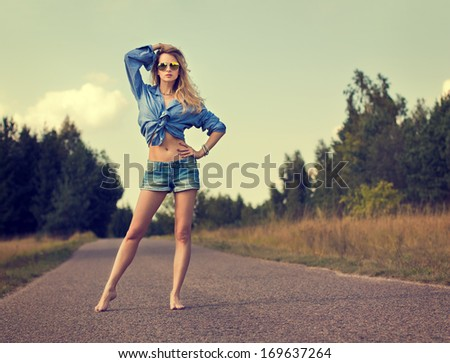 Full Length Portrait of Sexy Blonde Woman Standing on the Road. Toned Photo. Trendy Street Style. - stock photo