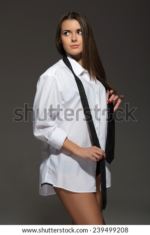 Full-length portrait of sexy young Caucasian brunette wearing men??s white shirt, tie and lingerie looking away isolated on grey background - stock photo