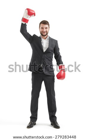 full length portrait of smiley businessman in formal wear and red boxing gloves raising up one hand and looking at camera. isolated on white background - stock photo