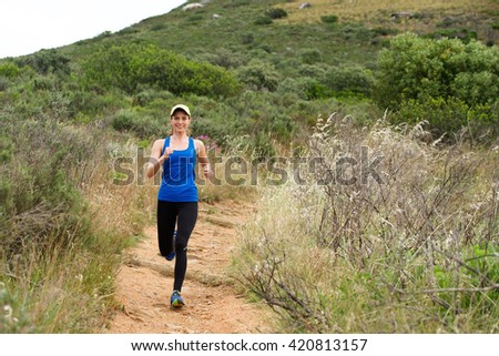 Full length portrait of smiling athletic woman running on dirt trail outside
