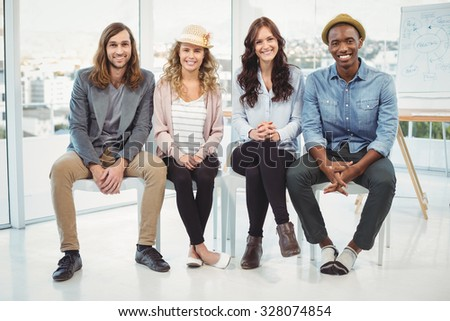 Full length portrait of smiling business people sitting on chair in office - stock photo