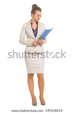 Full length portrait of smiling business woman looking on folder in hands