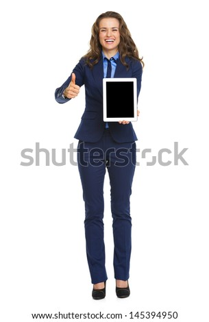 Full length portrait of smiling business woman showing tablet pc blank screen - stock photo