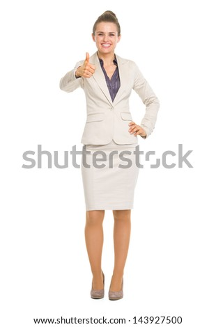 Full length portrait of smiling business woman showing thumbs up - stock photo
