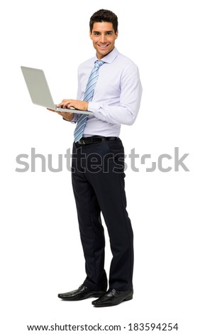 Full length portrait of smiling businessman with laptop standing isolated over white background. Vertical shot. - stock photo