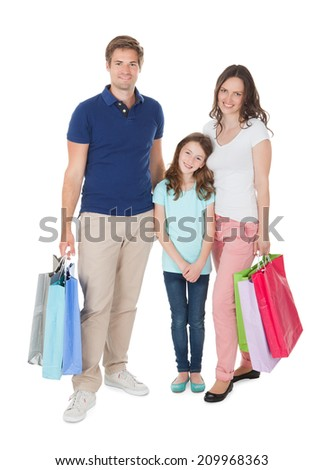 Full length portrait of smiling family with shopping bags standing over white background