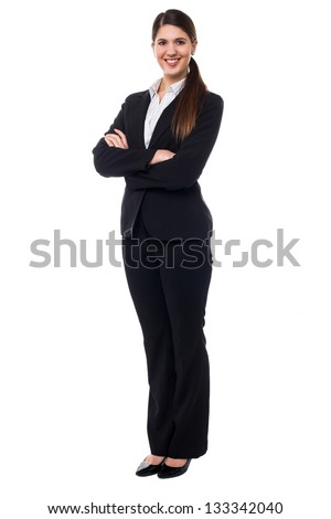 Full length portrait of smiling female executive posing with confidence, arms crossed. - stock photo