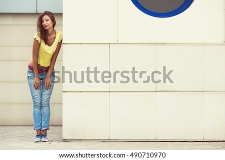 Full length portrait of smiling hipster girl wearing trendy  blue jeans, yellow knitted top near beige wall of modern building in summer city. Copy-space. Outdoor shot