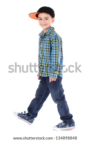 Full length portrait of smiling little boy in jeans and cup on white background