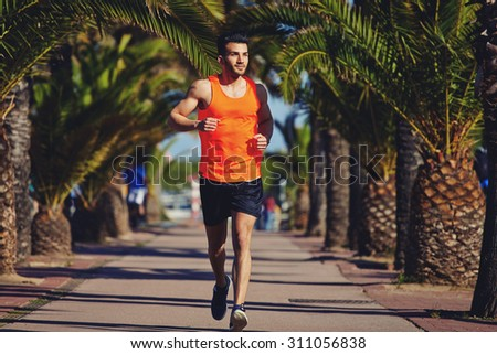 Full length portrait of smiling male runner with muscular body shape running outdoors at summer sunny evening, athletic man in workout wear jogging at palm lane with copy space area for text message - stock photo