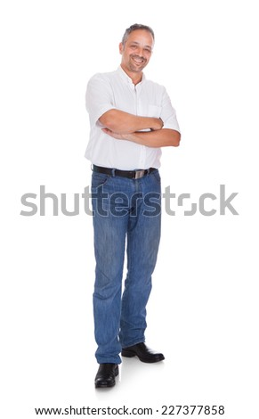 Full length portrait of smiling mature man standing arms crossed over white background - stock photo