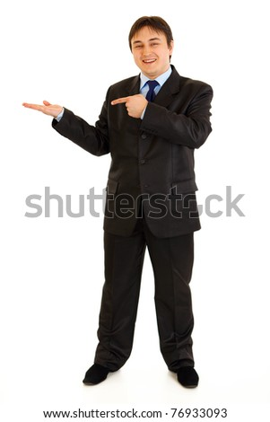 Full length portrait of smiling modern businessman pointing finger on empty hand isolated on white - stock photo