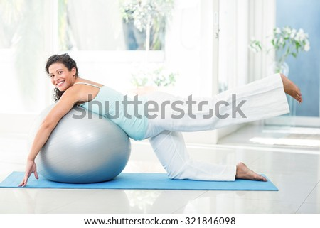 Full length portrait of smiling pregnant woman stretching with exercise ball on mat at fitness studio - stock photo