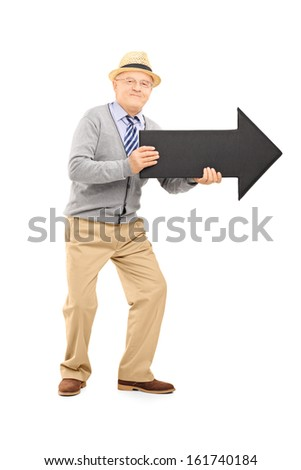 Full length portrait of smiling senior gentleman holding a big black arrow pointing to the right isolated on white background