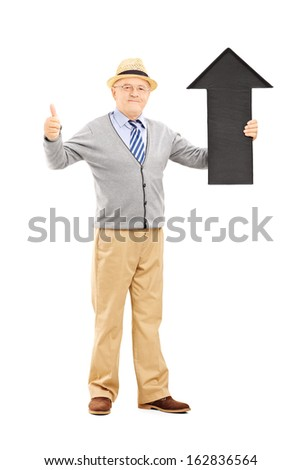 Full length portrait of smiling senior man holding a black arrow pointing up and giving a thumb up isolated on white background - stock photo