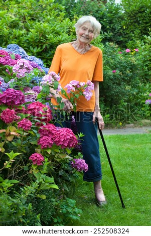 Full Length Portrait of Smiling Senior Woman Standing at the Flower Garden with Cane. - stock photo