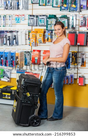 Full length portrait of smiling woman holding tool case in hardware store