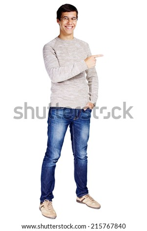 Full length portrait of smiling young man in glasses and beige sweater showing his pointing finger on something at side isolated on white background  - stock photo