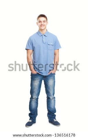 Full length portrait of smiling young man standing with hands in pockets isolated on white background - stock photo