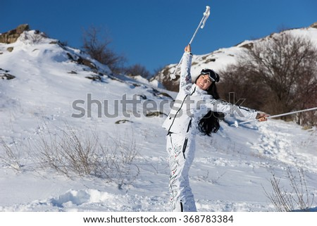 Full Length Portrait of Smiling Young Woman with Long Dark Hair Taking a Break from Skiing and Holding Poles Above Head, Happy Female Skier Celebrating Beautiful Day and Freedom