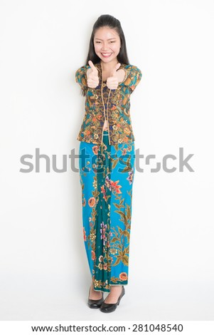 Full length portrait of Southeast Asian woman in batik dress thumbs up standing on plain background. - stock photo
