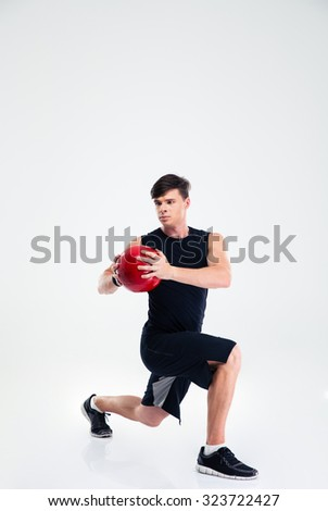 Full length portrait of sports man workout with fitness ball isolated on a white background