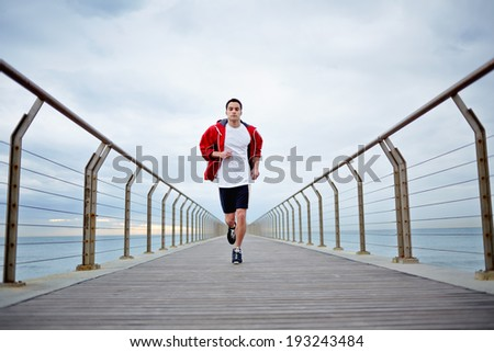 Full length portrait of sporty man running along beautiful pier with amazing sea horizon on background - stock photo