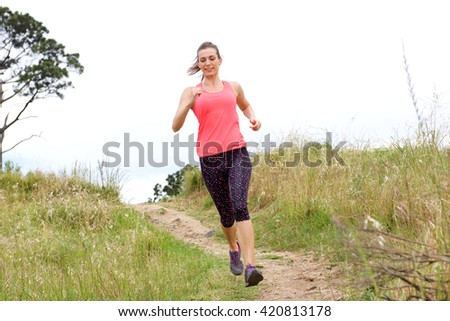 Full length portrait of sporty woman running on dirt path outdoors in park