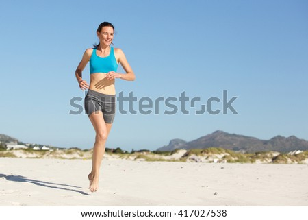 Full length portrait of sporty young woman running on the beach