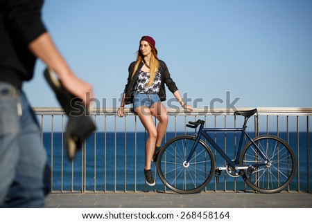 Full length portrait of stylish hipster girl standing with her sport fixed gear bike on the beach, young woman enjoying beautiful afternoon outdoors with blue sea on background, promenade at sunny day - stock photo