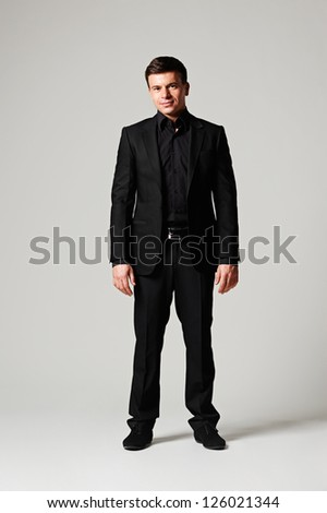 full length portrait of stylish man in black suit over grey background - stock photo