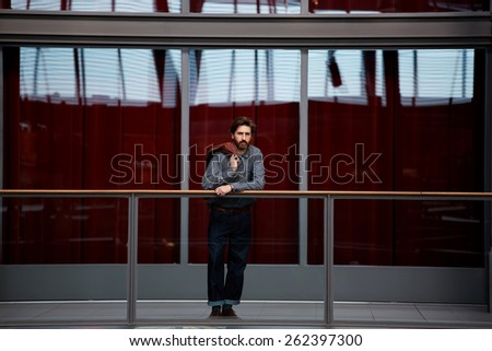 Full length portrait of stylish mature man standing in beautiful big hall with glassy red color wall on background, male clothing designer - stock photo