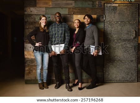 Full length portrait of successful business team standing in an office. Multiracial business professional posing for camera. - stock photo