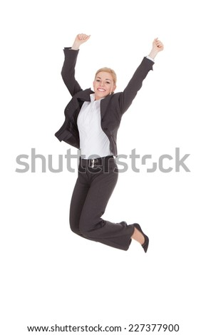 Full length portrait of successful businesswoman jumping against white background
