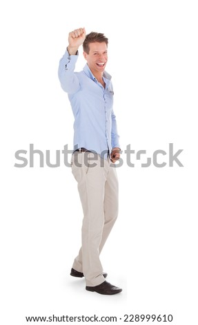 Full length portrait of successful man clenching fist against white background - stock photo