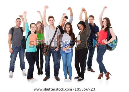 Full length portrait of successful university students with arms raised standing over white background