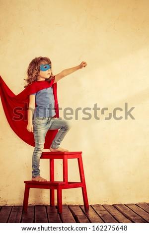 Full length portrait of superhero kid against grunge wall background - stock photo