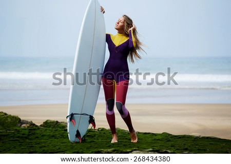 Full length portrait of surfer girl standing on the beach enjoying beautiful sunny day, sexy surfer girt holding her surfboard against ocean with beautiful waves on background - stock photo