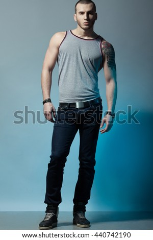 Full length portrait of tattooed brutal young man with short hair, bristle on face wearing sleeveless shirt, jeans, sneakers, posing over blue & gray background. Bully style. Studio shot